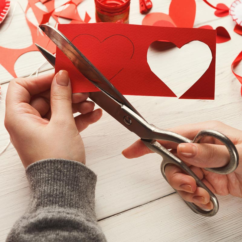 A photography of hands cutting red hearts out of red paper using scissors